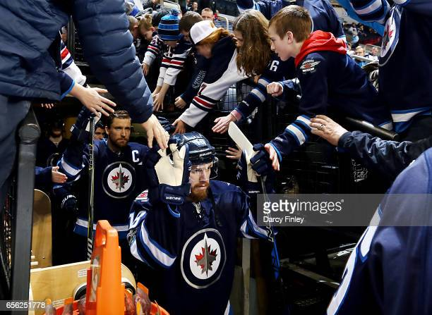 Bryan Little of the Winnipeg Jets high fives fans as he heads to the ice for the start of the pregame warm up prior to NHL action against the...