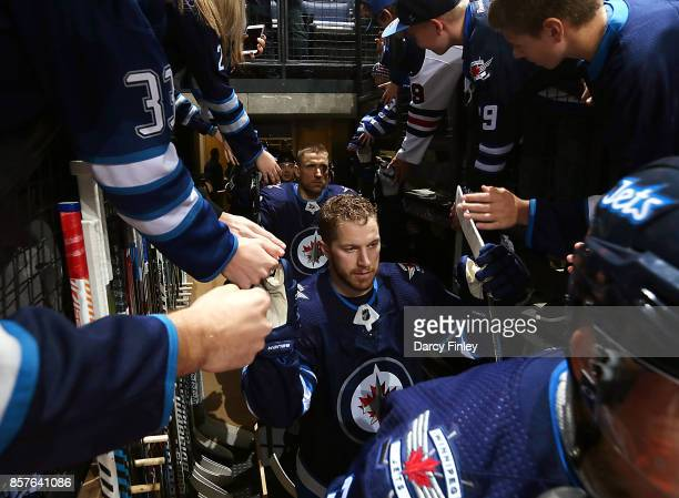 Bryan Little of the Winnipeg Jets high fives fans as he hits the ice for the pregame warm up prior to NHL action against the Toronto Maple Leafs at...