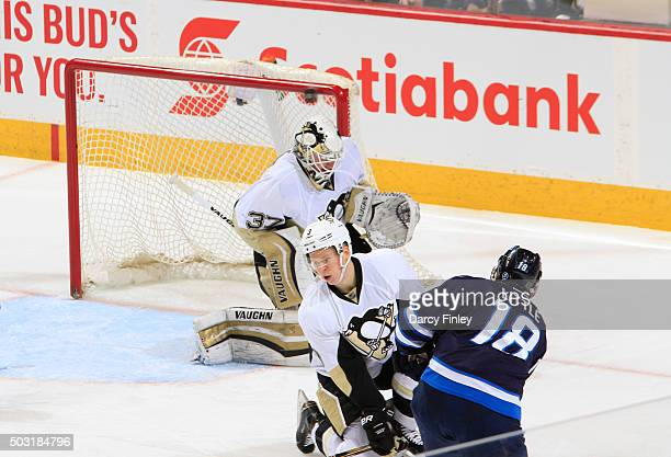 Bryan Little of the Winnipeg Jets hits the crossbar after taking a shot on goal over a defending Olli Maatta and goaltender Jeff Zatkoff of the...