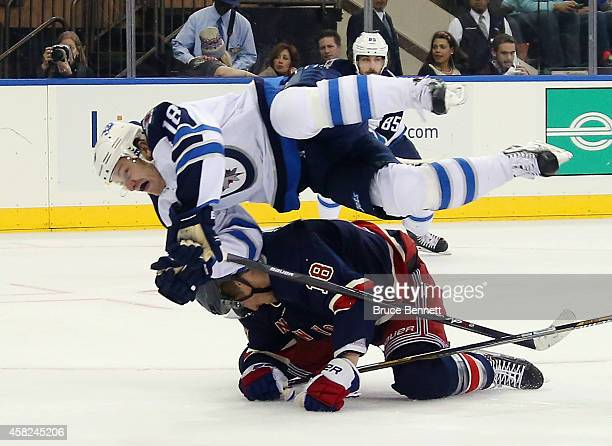 Bryan Little of the Winnipeg Jets hurdles over Marc Staal of the New York Rangers during the first period at Madison Square Garden on November 1 2014...