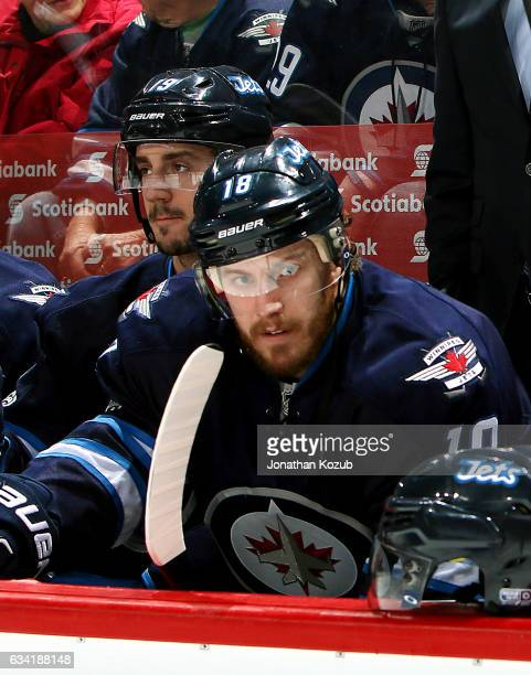 Bryan Little of the Winnipeg Jets looks on from the bench prior to puck drop against the Minnesota Wild at the MTS Centre on February 7 2017 in...