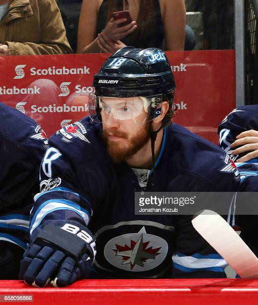 Bryan Little of the Winnipeg Jets looks on from the bench prior to puck drop against the Vancouver Canucks at the MTS Centre on March 26 2017 in...