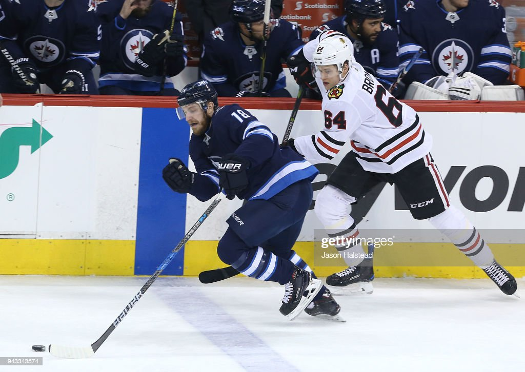 Bryan Little #18 of the Winnipeg Jets moves the puck in front of David Kampf #64 of the Chicago Blackhawks during NHL action on April 7, 2018 at Bell MTS Place in Winnipeg, Manitoba.