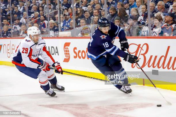 Bryan Little of the Winnipeg Jets plays the puck along the boards as Christian Djoos of the Washington Capitals defends during first period action at...