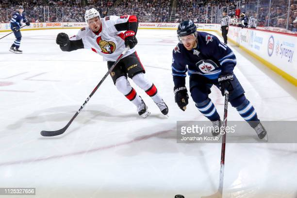 Bryan Little of the Winnipeg Jets plays the puck down the ice as Cody Ceci of the Ottawa Senators defends during the overtime period at the Bell MTS...