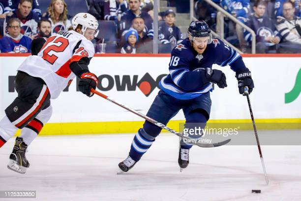 Bryan Little of the Winnipeg Jets plays the puck down the ice as Thomas Chabot of the Ottawa Senators defends during second period action at the Bell...