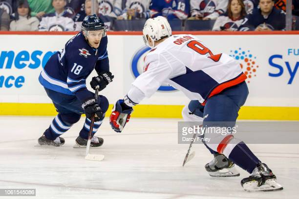 Bryan Little of the Winnipeg Jets plays the puck down the ice as Dmitry Orlov off the Washington Capitals defends during first period action at the...