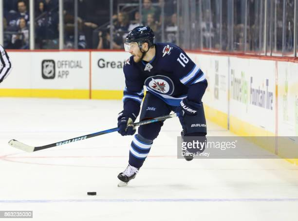 Bryan Little of the Winnipeg Jets plays the puck down the ice during first period action against the Carolina Hurricanes at the Bell MTS Place on...