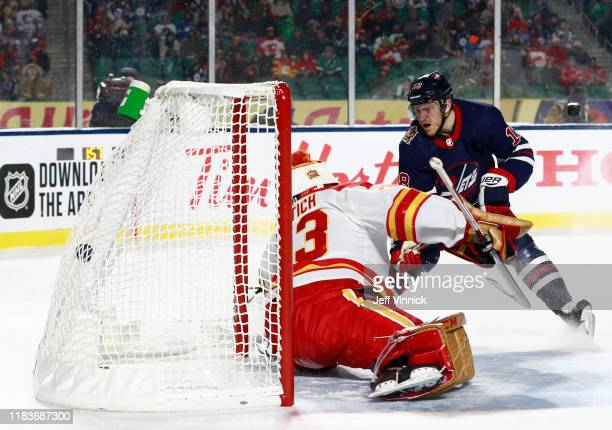 Bryan Little of the Winnipeg Jets scores the game-winning goal against goaltender David Rittich of the Calgary Flames in overtime during the 2019 Tim...