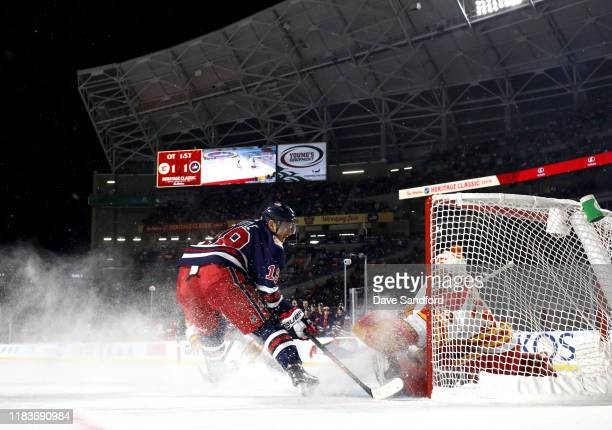 Bryan Little of the Winnipeg Jets scores the game-winning goal against goaltender David Rittich of the Calgary Flames as Derek Ryan looks on in...