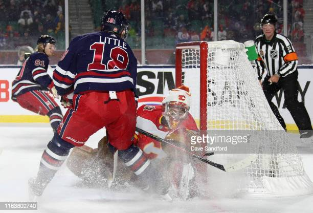 Bryan Little of the Winnipeg Jets scores the gamewinning goal against goaltender David Rittich of the Calgary Flames in overtime of the 2019 Tim...