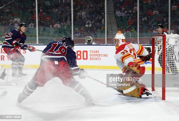 Bryan Little of the Winnipeg Jets scores the game-winning goal against goaltender David Rittich of the Calgary Flames on a pass by teammate Kyle...
