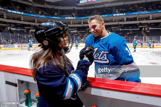 Bryan Little of the Winnipeg Jets shares a smile and a fist bump with the Trainer of the Game during the pregame warm up prior to NHL action against...