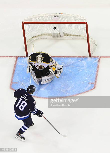 Bryan Little of the Winnipeg Jets shoots the puck behind goaltender Chad Johnson of the Boston Bruins and scores a shootout goal at the MTS Centre on...