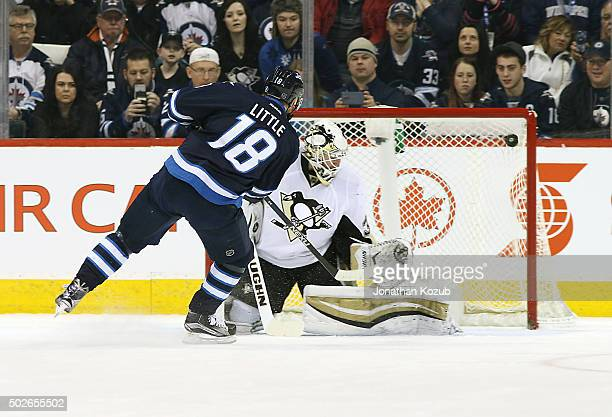 Bryan Little of the Winnipeg Jets shoots the puck into the top corner of the net as he scores on a penalty shot against goaltender Jeff Zatkoff of...