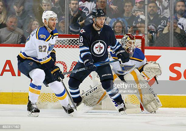Bryan Little of the Winnipeg Jets stands between Alex Pietrangelo and goaltender Pheonix Copley of the St Louis Blues as they keep an eye on the play...