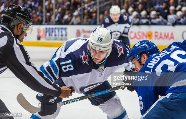 Bryan Little of the Winnipeg Jets takes a face off against Par Lindholm of the Toronto Maple Leafs during the first period at the Scotiabank Arena on...