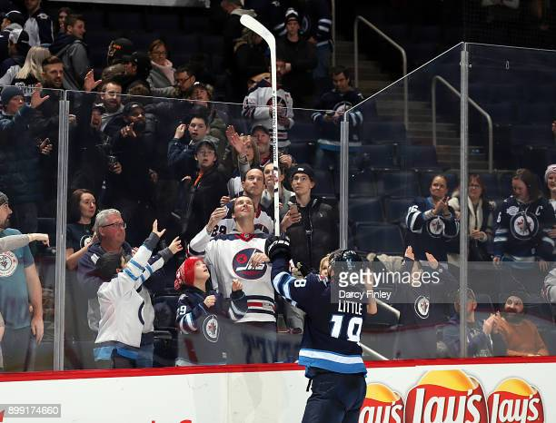 Bryan Little of the Winnipeg Jets throws a souvenir stick over the glass after receiving third star honors following a 43 victory over the Edmonton...