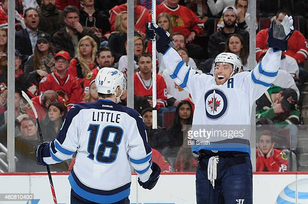 Bryan Little of the Winnipeg Jets turns to celebrate with Blake Wheeler after scoring against the Chicago Blackhawks in the first period during the...