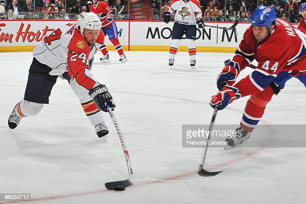 Bryan McCabe of the Florida Panthers battles for the puck with Roman Hamrlik of the Montreal Canadiens during the NHL game on March 25, 2010 at the...