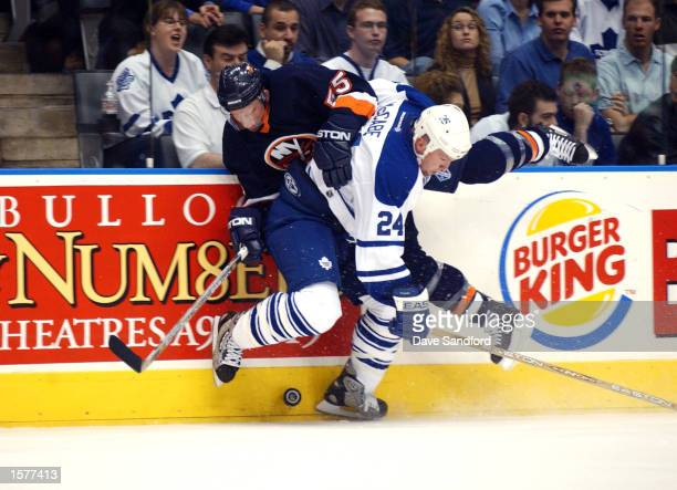 Bryan McCabe of the Toronto Maple Leafs checks Jason Blake of the New York Islanders during a game on April 18 2002 at the Air Canada Centre in...