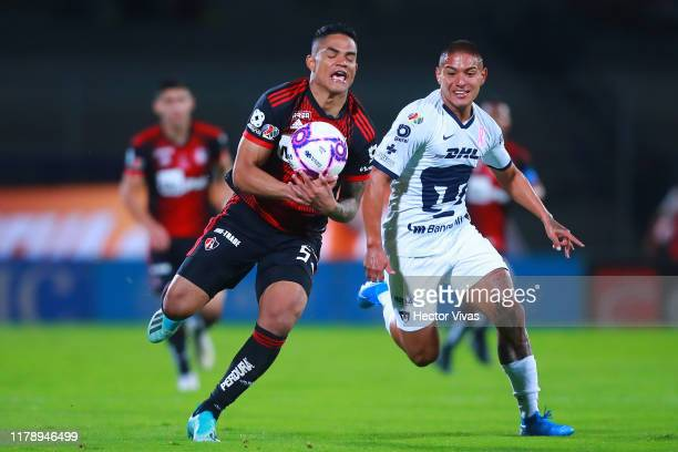 Bryan Mendoza of Pumas struggles for the ball with Anderson Santamaria of Atlas during the 16th round match between Pumas UNAM and Atlas as part of...