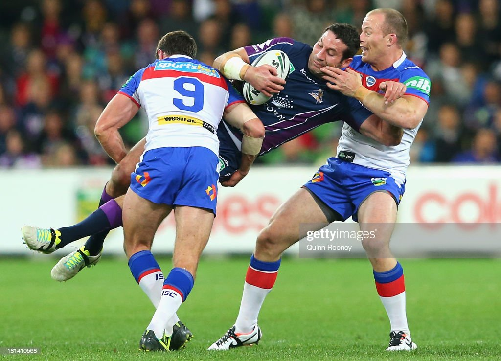Bryan Norrie of the Storm is tackled by Danny Buderus of the Knights during the NRL Second Semi Final match between the Melbourne Storm and the Newcastle Knights at AAMI Park on September 21, 2013 in Melbourne, Australia.