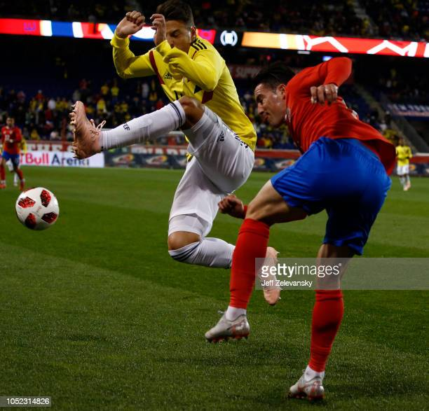 Bryan Oviedo of Costa Rica clears the ball in front of Santiago Arias of Colombia during their match at Red Bull Arena on October 16, 2018 in...