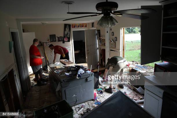 Bryan Parson Chris Gaspard and Derek Pelt help remove ruined items from Parson's home following flooding in the wake of Hurricane Harvey September 1...