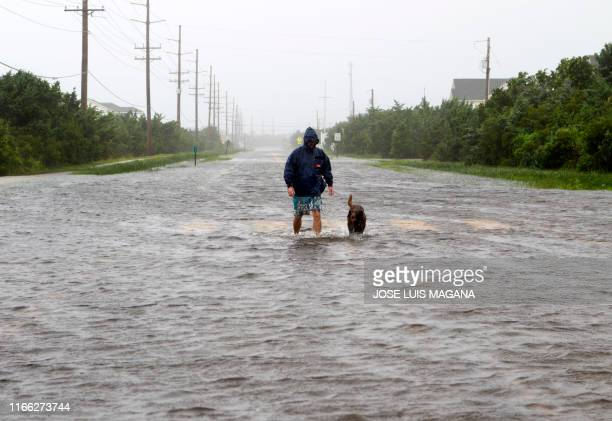 Bryan Philips walks with his dog on a flooded road in Salvo, North Carolina, as Hurricane Dorian hits the Outer Banks on September 6, 2019. - The...