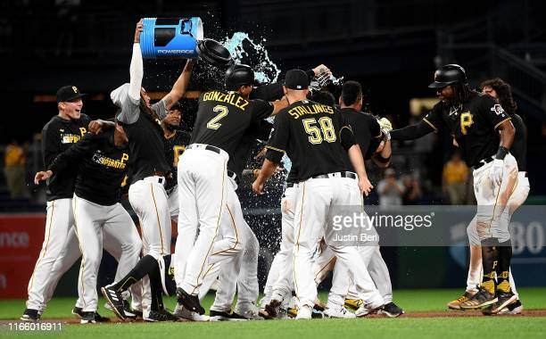 Bryan Reynolds of the Pittsburgh Pirates celebrates with teammates after hitting a walk off two run RBI single to give the Pirates a 6-5 win over the...