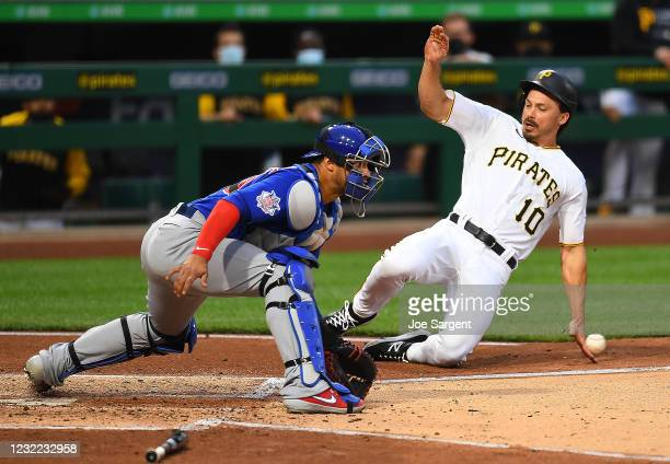 Bryan Reynolds of the Pittsburgh Pirates scores past Willson Contreras of the Chicago Cubs during the second inning at PNC Park on April 10, 2021 in...