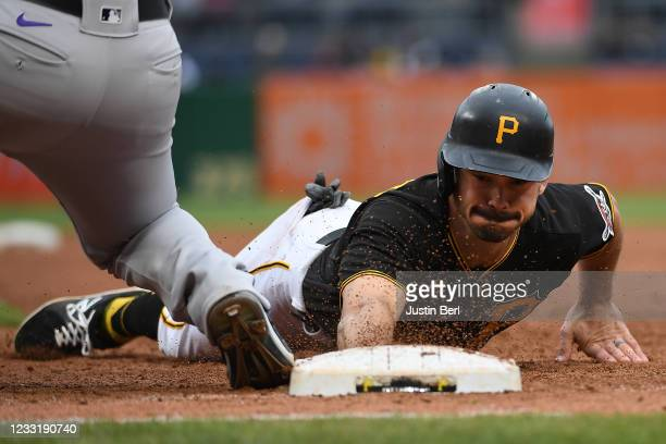 Bryan Reynolds of the Pittsburgh Pirates slides safely back to first base after a pickoff attempt by Daniel Bard of the Colorado Rockies in the...