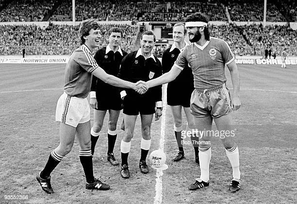 Bryan Robson captain of Manchester Untited shakes hands at the toss with Brighton captain Steve Foster prior to the FA Cup Final replay held at...