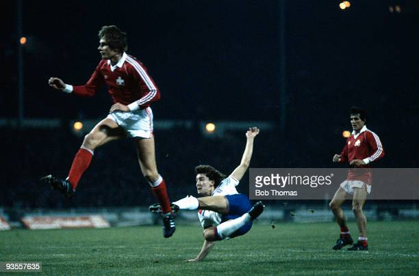 Bryan Robson of England takes a shot at goal despite the attention of Alain Geiger of Switzerland during the England v Switzerland World Cup...