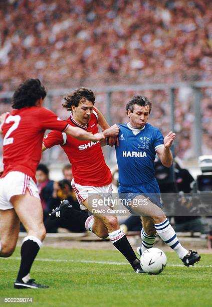 Bryan Robson of Manchester United challenges Peter Reid of Everton for the ball as John Gidman enters the frame during the 1985 FA Cup Final between...