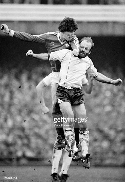 Bryan Robson of Manchester United outjumps Derby County captain Archie Gemmill during the FA Cup 5th Round match held at The Baseball Ground Derby on...