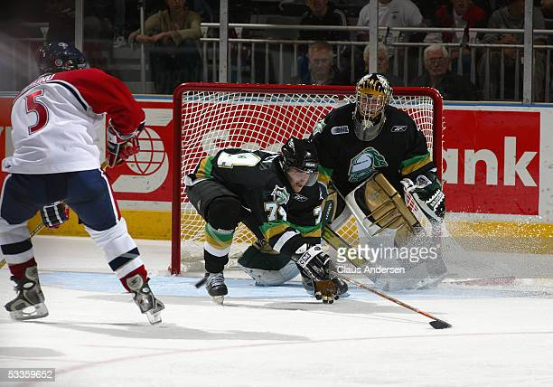 Bryan Rodney of the London Knights attempts to block a pass to Mitch Maunu of the Windsor Spitfires as goalie Ryan MacDonald of the Knights looks on...