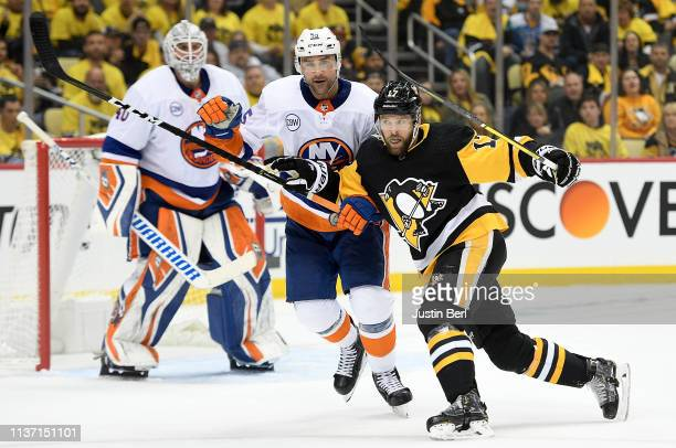 Bryan Rust of the Pittsburgh Penguins battles for position with Johnny Boychuk of the New York Islanders during the second period in Game Three of...