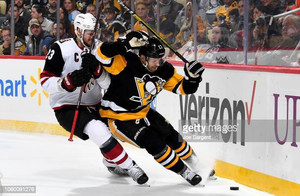 Bryan Rust of the Pittsburgh Penguins battles Oliver EkmanLarsson of the Arizona Coyotes at PPG Paints Arena on November 10 2018 in Pittsburgh...