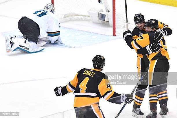 Bryan Rust of the Pittsburgh Penguins celebrates with Evgeni Malkin and Justin Schultz after scoring a first period goal against Martin Jones of the...