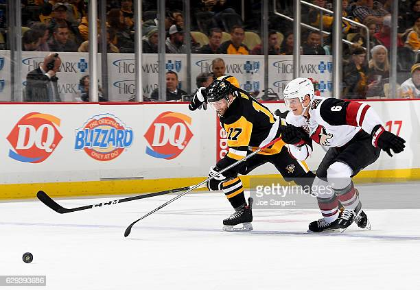 Bryan Rust of the Pittsburgh Penguins handles the puck against Jakob Chychrun of the Arizona Coyotes at PPG Paints Arena on December 12 2016 in...