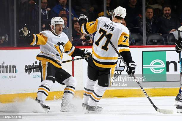Bryan Rust of the Pittsburgh Penguins is congratulated by his teammate Evgeni Malkin after scoring a goal against the New York Islanders during the...
