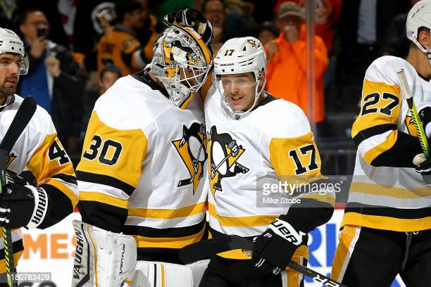 Bryan Rust of the Pittsburgh Penguins is congratulated by his teammate Matt Murray after scoring a game-winning goal against the New York Islanders...