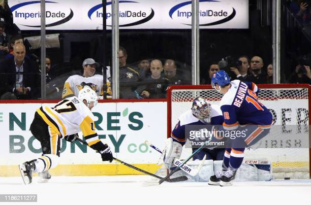 Bryan Rust of the Pittsburgh Penguins scores the game winning goal at 3:25 of overtime against Semyon Varlamov of the New York Islanders at the...