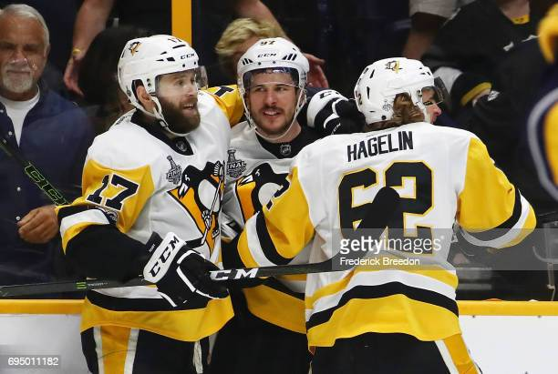 Bryan Rust Sidney Crosby and Carl Hagelin of the Pittsburgh Penguins celebrate against the Nashville Predators during the third period in Game Six of...