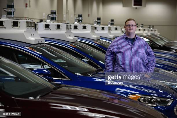Bryan Salesky chief executive officer of Argo AI stands for a photograph next to modified Ford Motor Co Fusion autonomous vehicle parked in a garage...