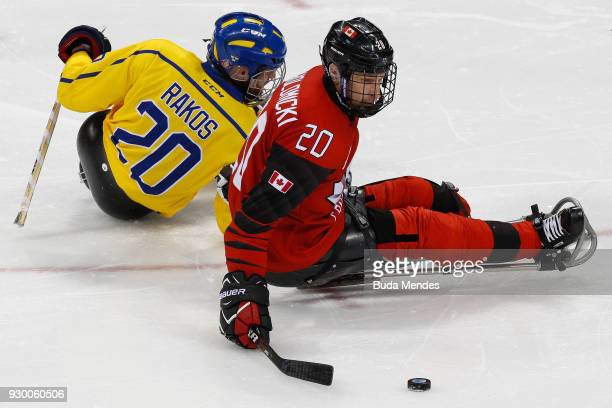 Bryan Sholomicki of Canada battles for the puck with Niklas Rakos of Sweden in the Ice Hockey Preliminary Round Group A game between Canada and...