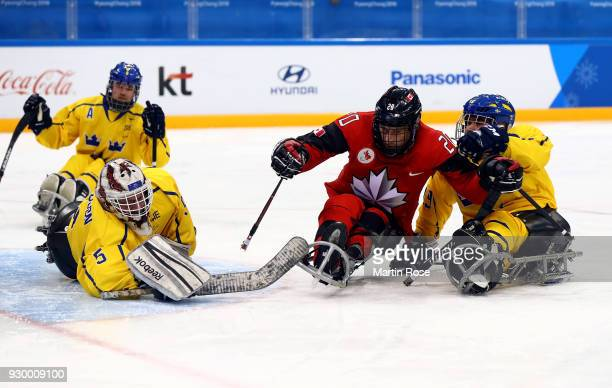 Bryan Sholomicki of Canada fails to score over Ulf Nilsson goaltender of Sweden in the Ice Hockey Preliminary Round Group A game between Canada and...