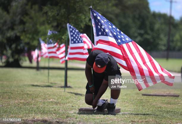 Bryan Smart places American flags along the road leading past the Fountain of Praise church where services will be held for George Floyd on June 7...